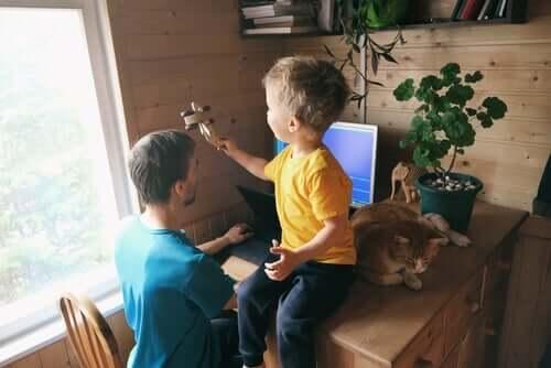 En pappa väljer att arbeta hemifrån med sin son bredvid