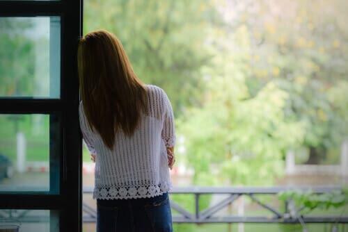 En kvinna som ser ut genom ett fönster