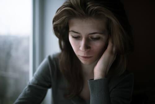 En ledsen kvinna ser ner