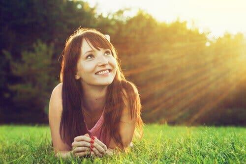 En leende tjej ligger i gräset och tänker på relationen mellan optimism och hälsa