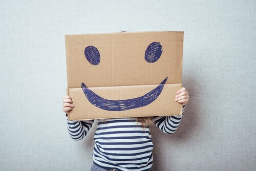 Ett barn bakom en kartong med smiley