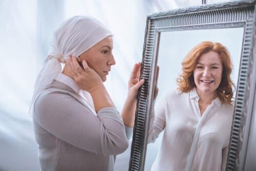 En kvinna med cancer ser sig själv, så som hon såg ut med hår, i spegeln