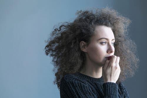 En kvinna med krulligt hår ser ut i tomrummet och muttrar farliga ord