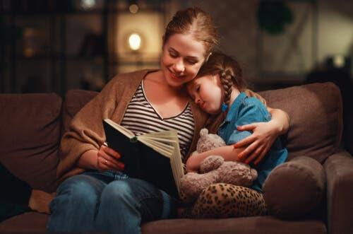 En mamma i soffan läser med sin dotter