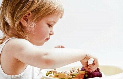 En flicka som äter grönsaker, helt på egen hand