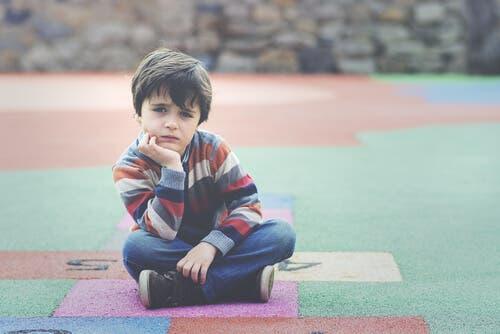 En pojke sitter på marken och tänker på WISC-testet som verktyg