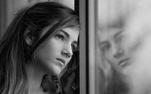 An autistisk människa ser ut genom ett fönster
