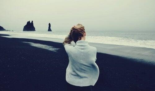 En kvinna vid stranden en mulen dag