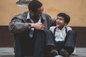 En far med son sitter tillsammans på en trottoar och skrattar
