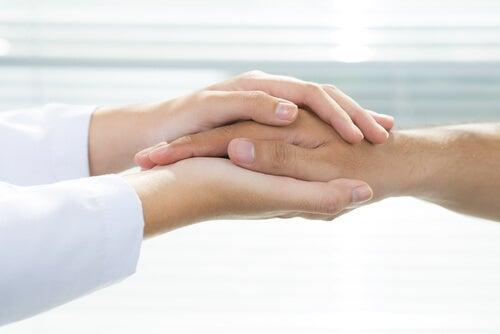 En läkare som håller en patients händer, representerar allmän sjukvård