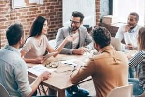 En grupp anställda sitter runt ett bord för ett kontorsmöte