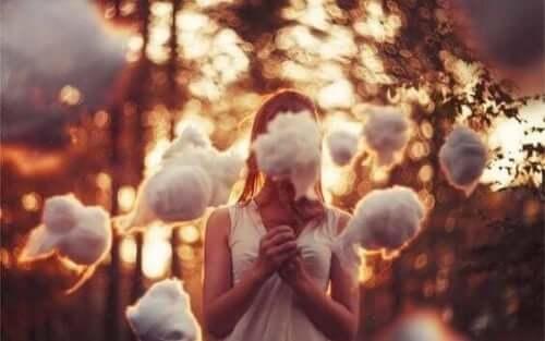 En kvinna med små moln framför ansiktet