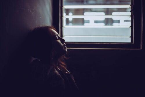 En kvinna vid ett fönster kontemplerar rädslan för det okända