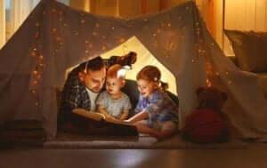 En lycklig stund: far läser för barnen i ett vardagsrumstält