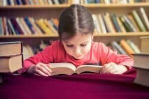 En liten flicka i fart med att lära sig läsa
