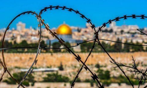 En bild av Jerusalem genom ett taggtrådsstängsel som exempel på heliga värderingar