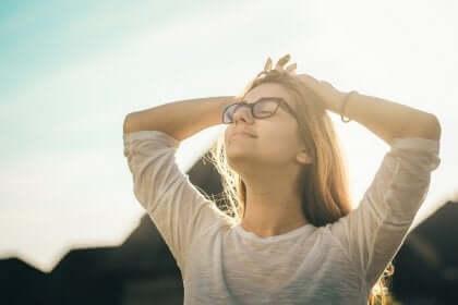 En kvinna med slutna ögon ler i solskenet