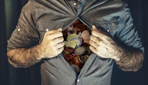 En man med mynt där hjärtat ska vara
