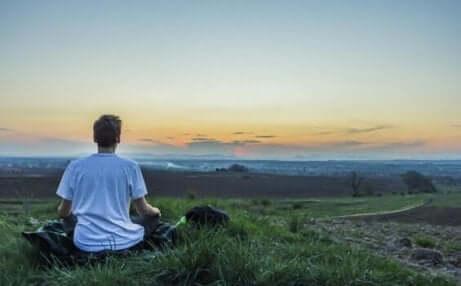 En man som försöker utöva vipassanameditation på en öppen landsbyggd