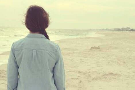 En kvinna står på stranden och ser ut över havet