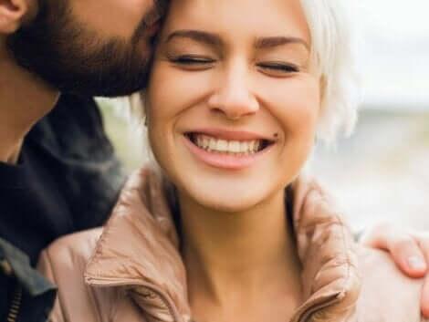 En man som kysser en kvinna på sidan av hennes huvud