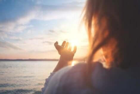 En kvinna ser ut över spegelblankt vatten i gryningen