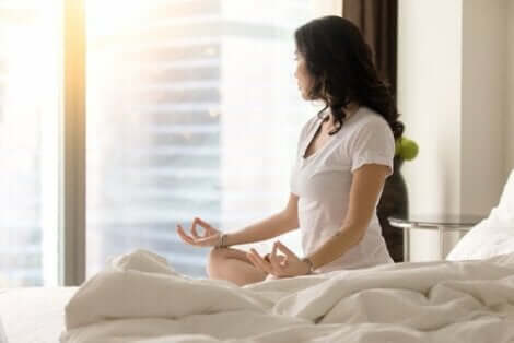En kvinna som mediterar i sängen