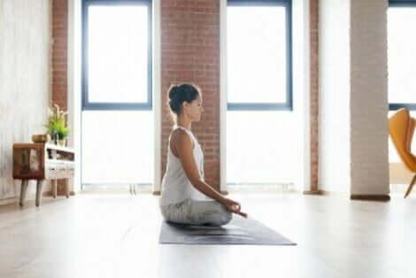 En kvinna som utövar meditation hemma