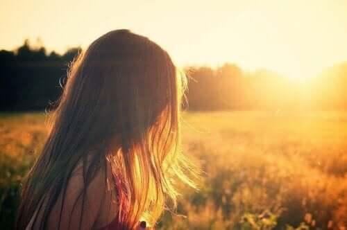 En kvinna i ett fält med solnedgången framför sig
