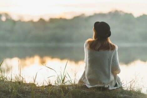 Kvinna njuter av enkelheten vid en insjö