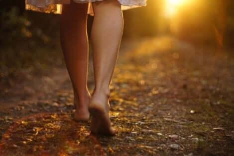 En kvinna som går barfota nerför en stig