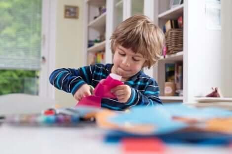 En pojke klipper i papper med en sax
