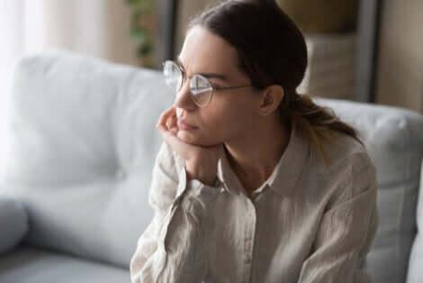 En kvinna i glasögon funderar
