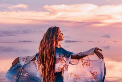 En kvinna vid havet i solnedgången