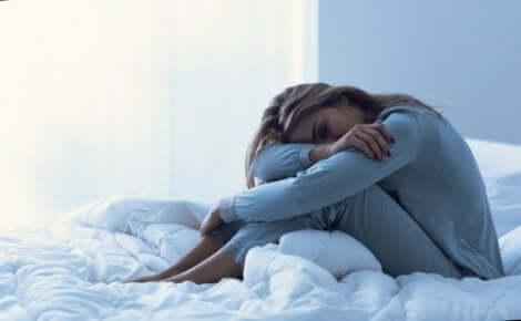 En utmattad kvinna sitter och sover i sängen