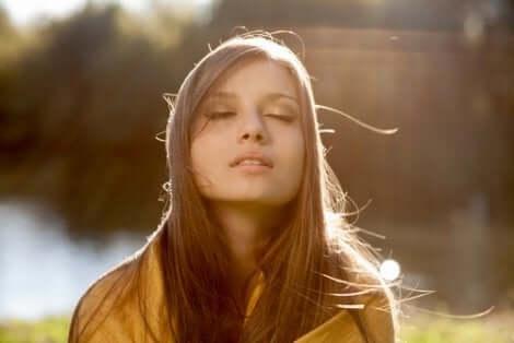 En kvinna med slutna ögon njuter av solskenet: Slow living för ett lyckligare liv.