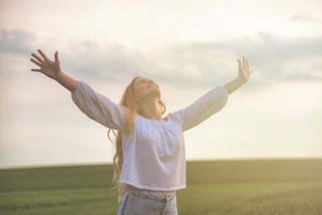 En lycklig kvinna på öppna fält med utsträckta armar