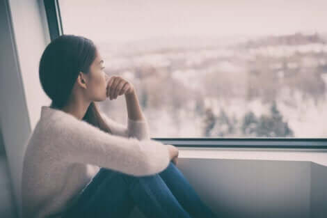 Deprimerad kvinna vid fönster