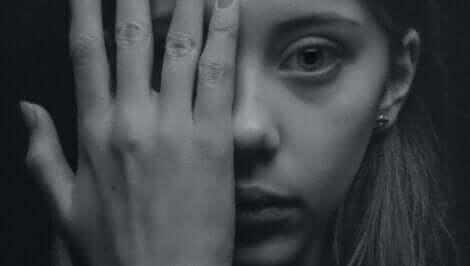 En kvinna som täcker sitt ansikte med handen