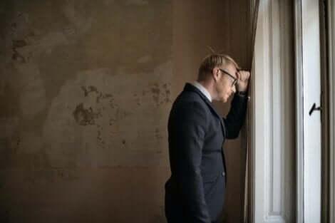 En man vid ett fönster som försöker acceptera sina brister