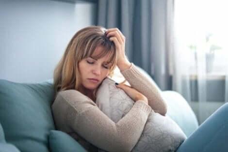 En sorgsen kvinna vilar i en soffa