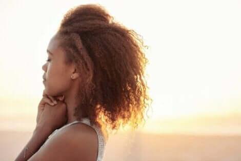 En kvinna som övar emotionell självreglering under solnedgången