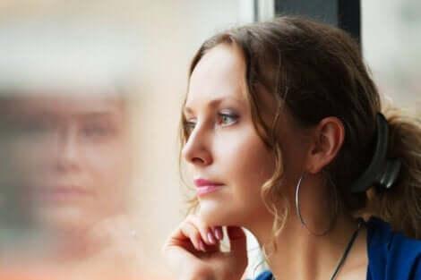 En kvinna som tittar ut genom fönstret.