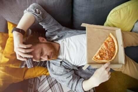 En uttråkad man som äter pizza på soffan