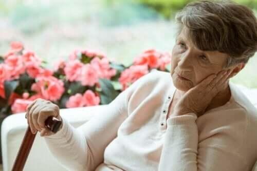 En äldre dam sitter på en soffa framför blommor