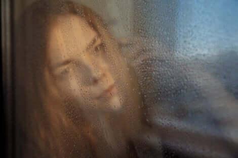 En kvinna som tittar ut genom ett regnigt fönster