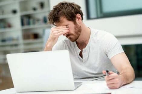 En trött kille som arbetar på sin bärbara dator