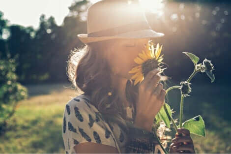 En kvinna som luktar på en solros