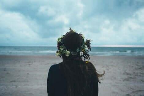 En ensam kvinna med blomkrans i håret på en strand