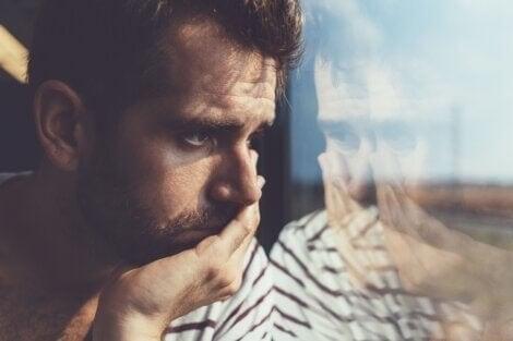 En ledsen kille som tittar ut genom tågfönstret
